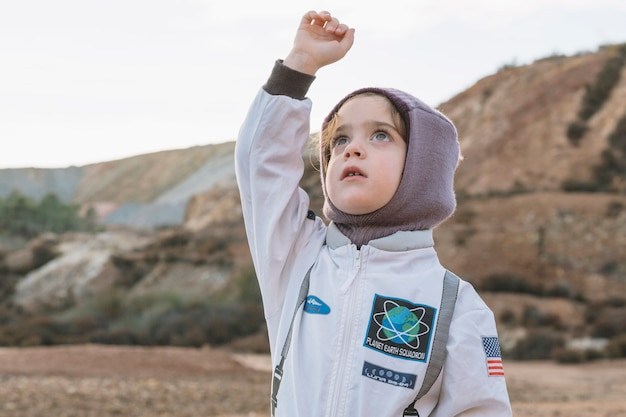 Little girl in spaceman suit in nature Free Photo