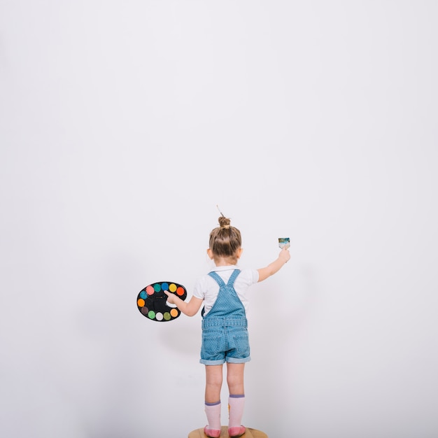Little girl standing on chair and painting wall with brush Free Photo