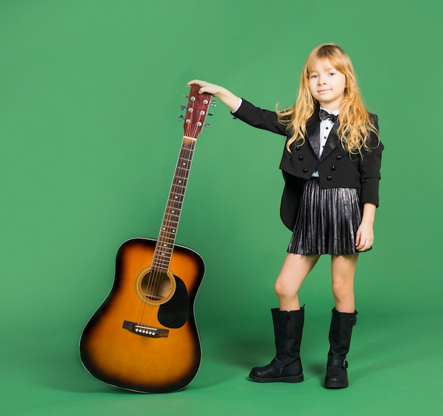 Little girl standing with acoustic guitar Free Photo