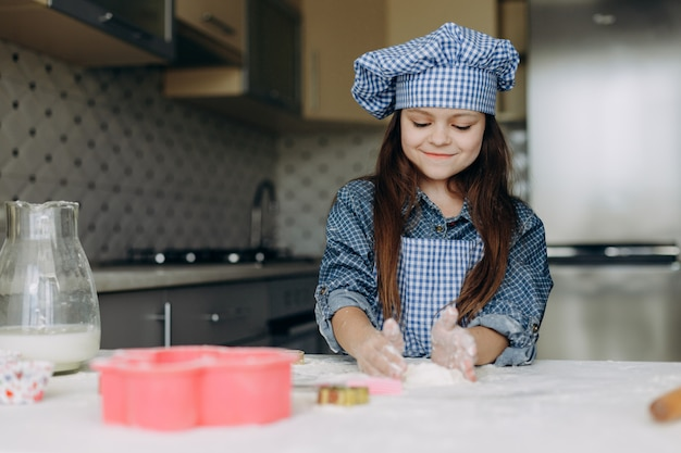 Маленькая девочка размешивает тесто внимательно и с удовольствием Premium Фотографии