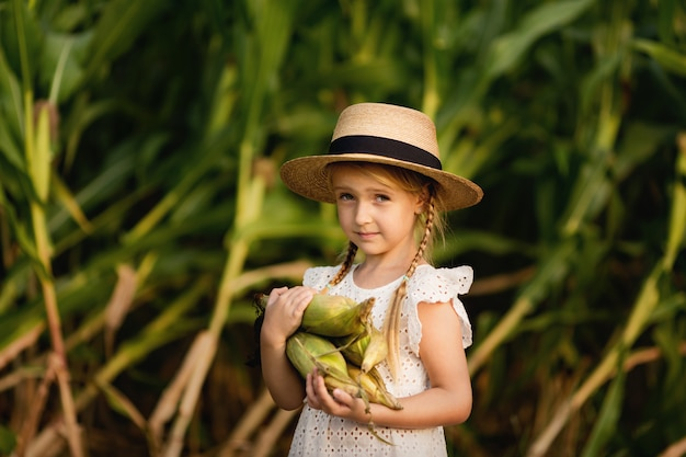 Little girl in straw hat holding corncobs Premium Photo