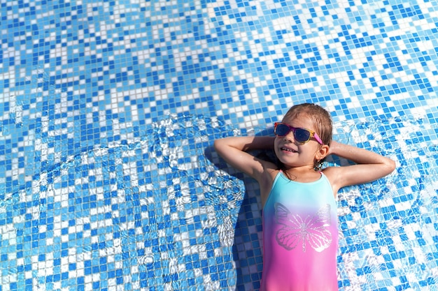 Little girl in sunglasses and hat with unicorn in outdoor swimming pool of luxury resort on summer vacation on tropical beach island Premium Photo