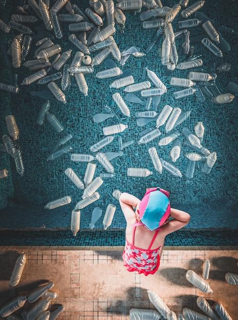 Little girl and swimmpool full of plastic bottles Premium Photo