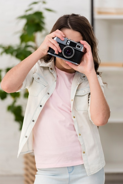 Little girl taking a photo with a camera Free Photo