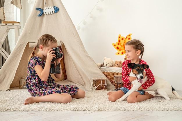 Маленькая девочка фотографирует друга, обнимающего собаку фокстерьера, сидящего на полу в игровой комнате Premium Фотографии