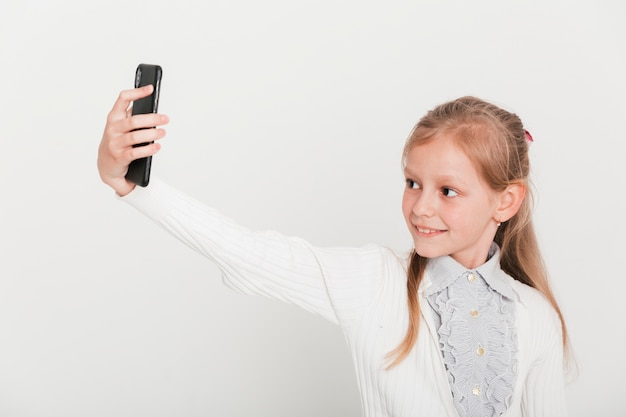 Little girl taking selfie with smartphone Free Photo