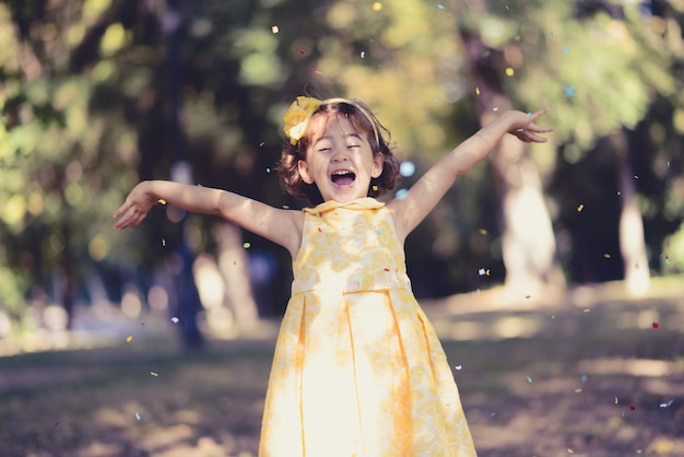 Little girl throwing confetti in the air Free Photo
