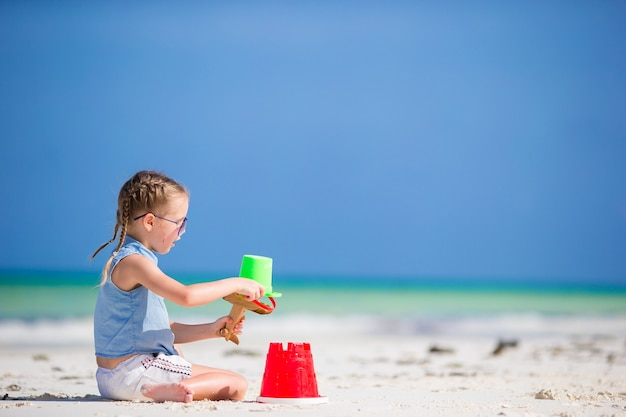 Little girl at tropical white beach making sand castle Premium Photo