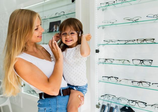 Little girl trying on glasses frame Free Photo