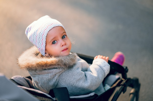 The little girl turns back sitting in a baby carriage on a walk in the park. Premium Photo