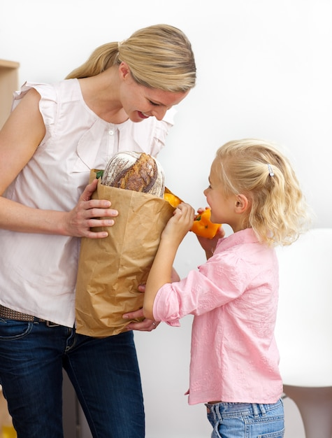 Маленькая девочка, распаковывающая продуктовый портфель с матерью Premium Фотографии