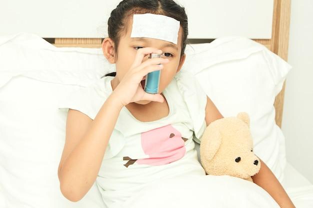 Little girl using asthma inhaler Premium Photo