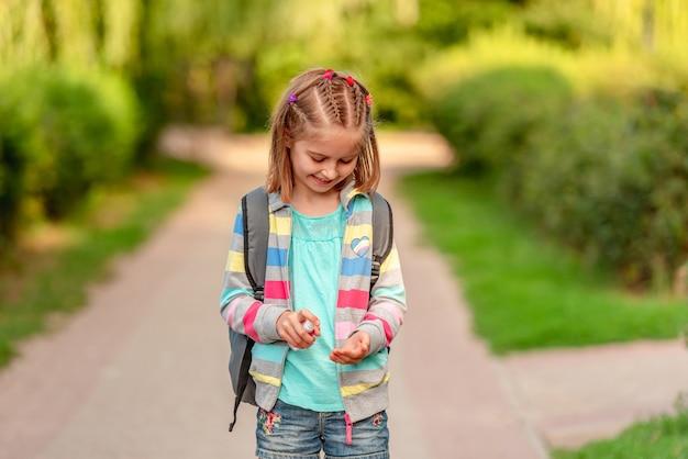 公園で放課後手の消毒剤を使用して小さな女の子 Premium写真