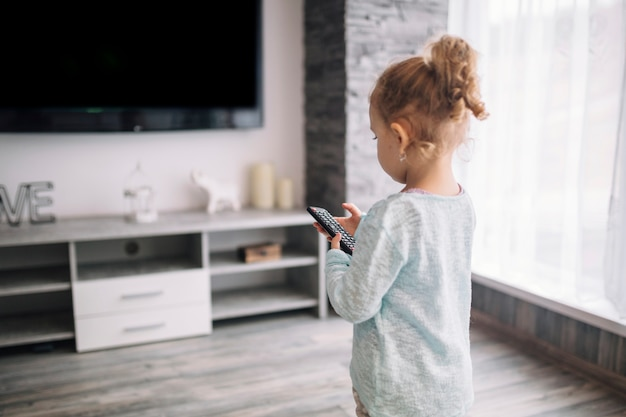 Little girl using tv remote Free Photo