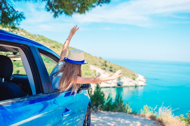 Little girl on vacation travel by car on beautiful landscape Premium Photo