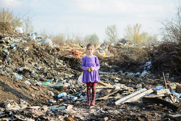 Little girl in a violet dress and red striped tights strands in a city dump among piles of garbage holding yellow faded flowers Premium Photo