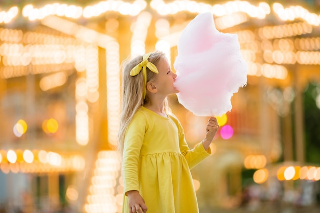 Little girl on a walk in an amusement park eating cotton candy Premium Photo