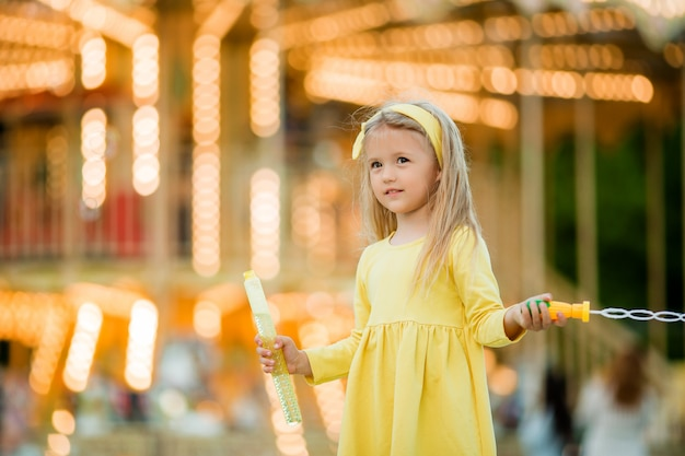 Little girl on a walk in an amusement park with soap bubbles Premium Photo