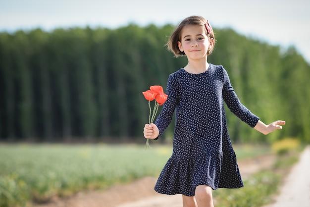 Little girl walking in nature field wearing beautiful dress Free Photo