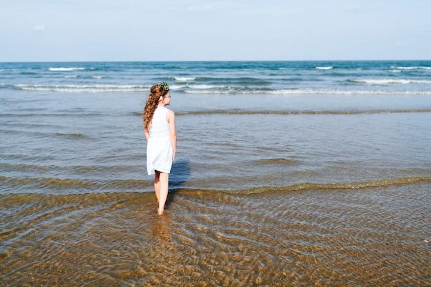 Little girl walking in the water Free Photo