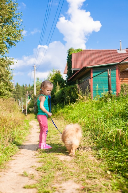 Little girl walking with her dog on a leash Premium Photo
