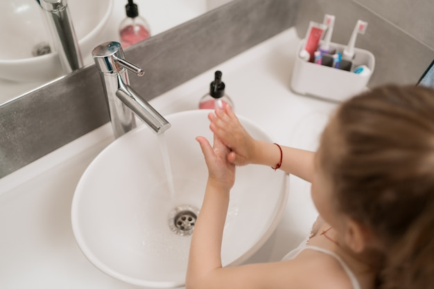 Little girl washing hands with soap Free Photo