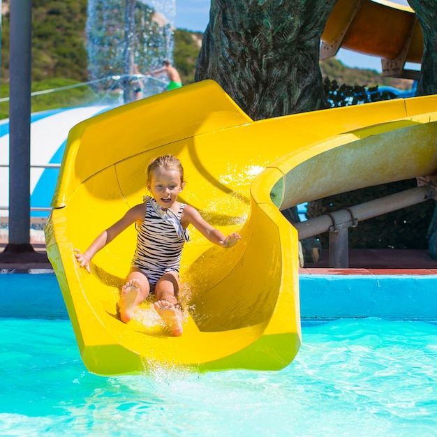 Little girl on water slide at aquapark during summer holiday Premium Photo