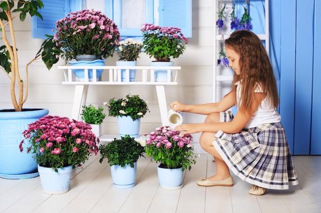 The little girl watering flower pots. Premium Photo