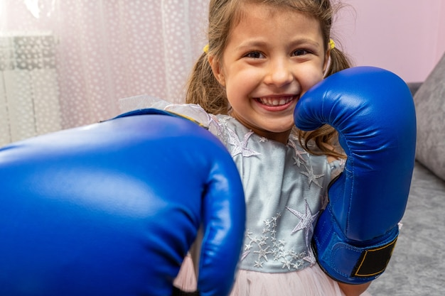 Little girl wearing blue boxing gloves and a holiday dress with stars Premium Photo