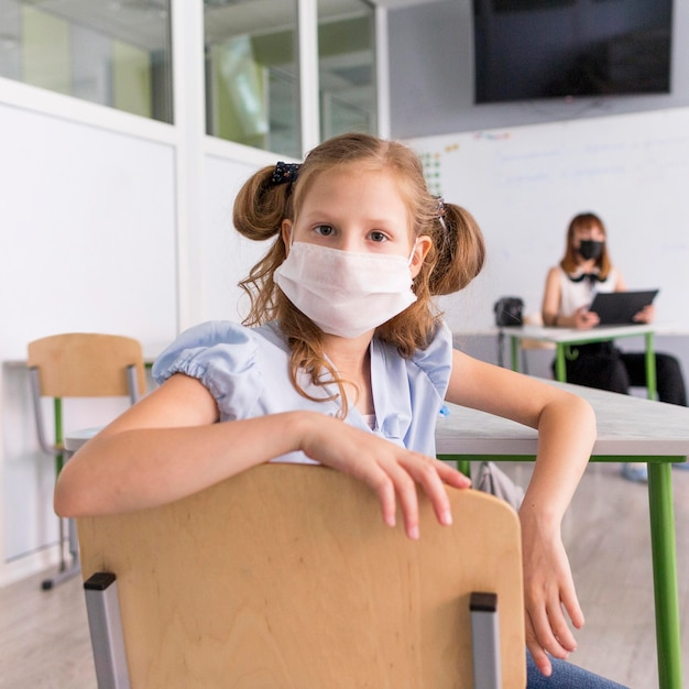 Little girl wearing a face mask during pandemic Free Photo