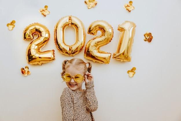 웃 고, 장난하는 골드 무도회 안경을 쓰고 어린 소녀 프리미엄 사진