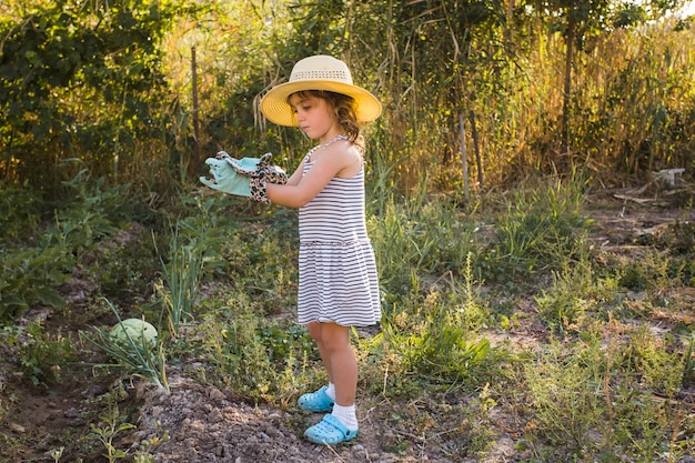 Little girl wearing hat standing in the field Free Photo