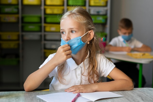 Bambina che indossa una mascherina medica in classe Foto Gratuite