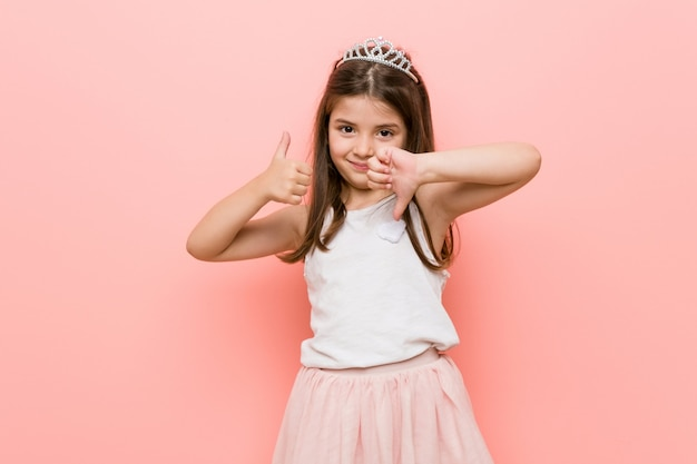 Little girl wearing a princess look showing thumbs up and thumbs down, difficult choose Premium Photo