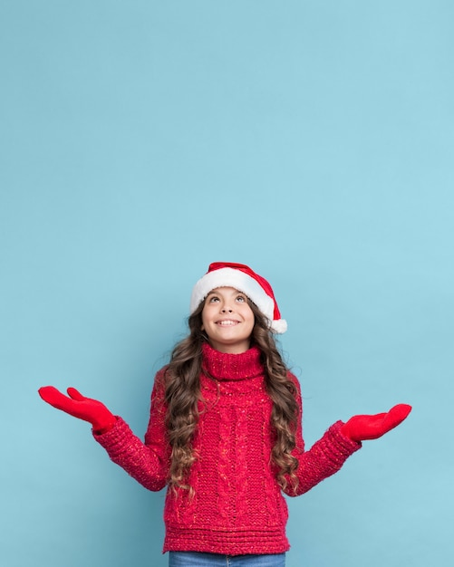 Little girl wearing sweater and christmas hat Free Photo