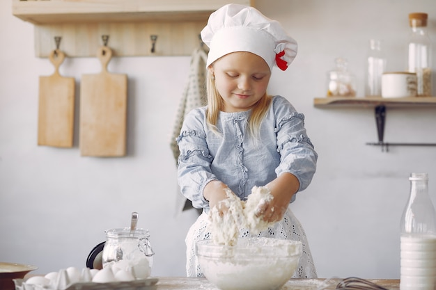 Little girl in a white shef hat cook the dough for cookies Free Photo