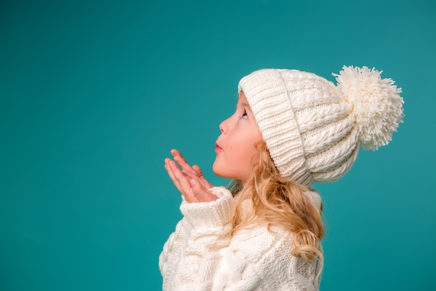Little girl in white winter knitted hat and sweater on blue Premium Photo