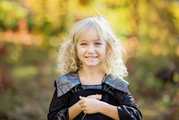 Little girl in witch costume celebrate halloween outdoor and have fun. Premium Photo