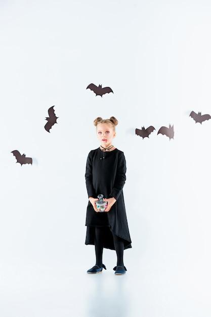 Маленькая девочка-ведьма в черном длинном платье и волшебных аксессуарах. хэллоуин Бесплатные Фотографии