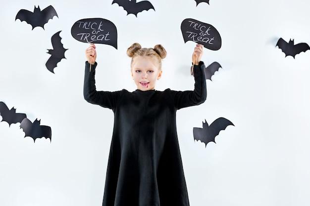 黒のロングドレスと魔法のアクセサリーの少女魔女。 無料写真