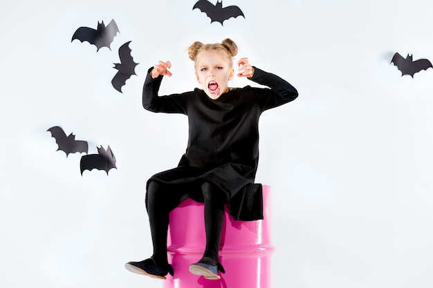 Маленькая девочка-ведьма в черном длинном платье и волшебных аксессуарах. Бесплатные Фотографии