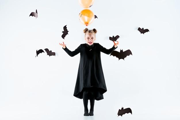 검은 긴 드레스와 마법의 액세서리에 어린 소녀 마녀 무료 사진