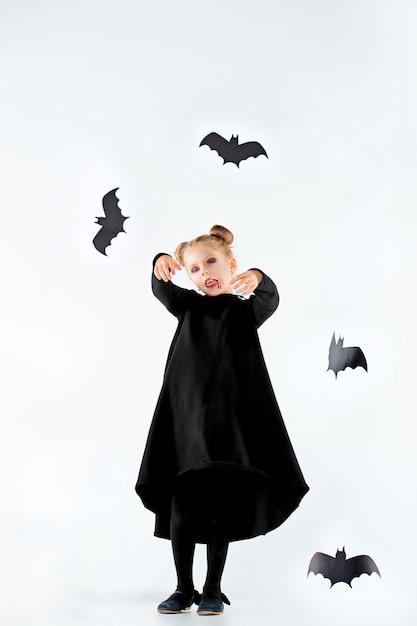 Маленькая девочка-ведьма в черном длинном платье и волшебных аксессуарах Бесплатные Фотографии