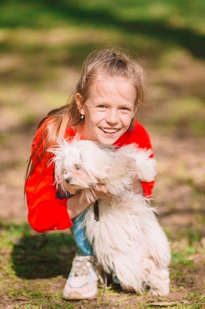 Маленькая девочка с белым щенком. щенок на руках у девочки Premium Фотографии