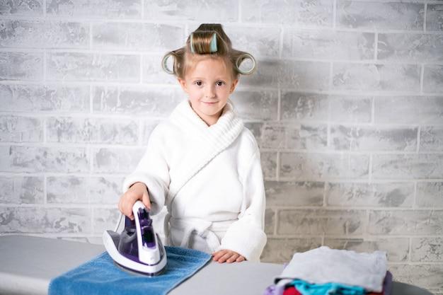 アイロンをかけられる洗濯物の量を持つ少女、彼女の頭にカーラーが付いている白いコート Premium写真
