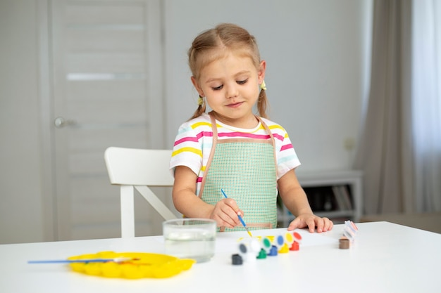 Little girl with apron painting Free Photo