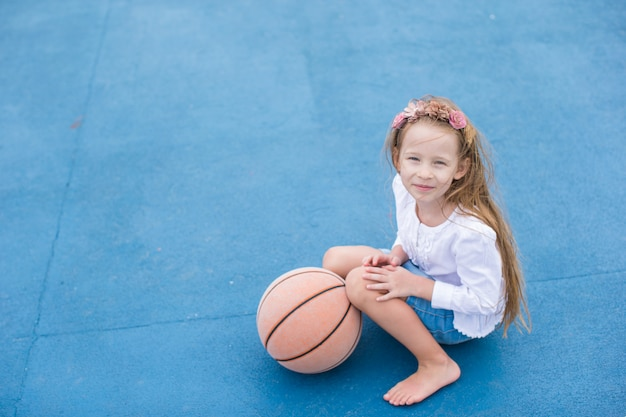 Little girl with basketball on the outdoor court at tropical resort Premium Photo