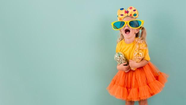Маленькая девочка в больших очках с конфетами Premium Фотографии