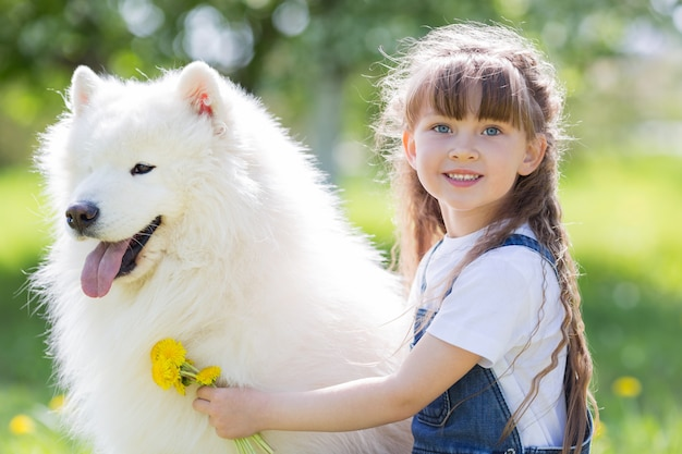 Little girl with a big white dog in the park. Premium Photo