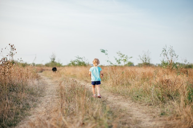 Маленькая девочка с черной собакой, ходить на поле обратно в камеру в жаркий летний вечер. Premium Фотографии